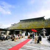 広い空の下執り行われる、濱田邸前枕木広場での神前式