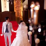 キャンドルの明かりが揺れるなか、彼の待つ誓いの場へと進む。美しい花嫁姿にはゲストの視線もくぎづけに!
