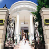 門をくぐるとそこには緑とプールが広がる白亜の邸宅。邸宅全てを貸切にできるので、ゲストを囲んでのアットホームウェディングが叶う・・・。