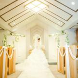 温もりの溢れる、白と木目調のフラワーチャペル。大理石のバージンロードがドレスをより一層美しく際立たせる。