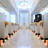 セントマリエール教会 全面白を基調としたチャペル モザイクタイルの輝きと光のシャワーを浴びて、ロマンチックな教会式 9mのバージンロード、天井高6.5mを参列者に見守られ入場して頂きます