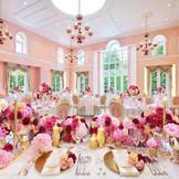 【メゾン・ドゥ・フロール~フランス館~】 淡く上品なサーモンピンクの内装がゲストの祝福気分を盛り上げる。大きなフランス窓からはやわらかな陽光が降り注ぎ、幸せな花嫁の笑顔をより輝かせてくれる。