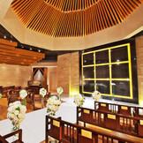 【チャペル】 建築デザイナーマーク伊東氏と照明デザイナー金田篤士氏が手がけた花嫁の美しさを引き出す空間。シャープさの中に温かさを感じるスタイリッシュでモダンな構造。上質感あふれる石と木に包まれた聖壇が、主役のおふたりを輝かせる。