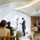 たくさんのゲストに暖かく見守られながら、 光の十字架の前で永遠の愛を誓う。 純白のウエディングドレスに身を包んだ花嫁様はやわらかい光に包まれます。