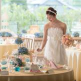 ブルー&イエロー&ピンクのパステルコーディネートも、バランスを考えれば甘すぎないナチュラルコーディネートに。花嫁のウエディングドレスが際立つテーブルセッティング