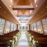 祭壇奥のガラス窓は高さ12Mもの天井まで届く。堂内にいながらも鋤透き通る青空と太陽の輝きがたっぷりと感じられ、開放感に満ち溢れている。