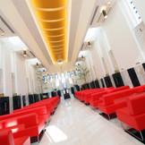 光溢れる白い空間にスカーレットのベンチシートが鮮やかなチャペル ブランアンジュ。