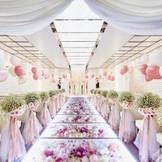 花々が敷き詰められたガラスのバージンロードが美しいチャペルで、幻想的な挙式を叶えて