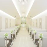 白を貴重にした式場は、正面に映像システム完備。小さめのシャンデリアと壁のモザイクボードはかわいらしさを表現。