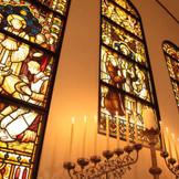 イギリスの教会で実際に使われてきたステンドグラスや燭台といった調度品が配された荘厳な雰囲気。 英国で長い歴史を重ねてきたステンドグラスに見守られ、厳粛なステージでふたりの「愛」を誓って。