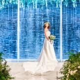 自然光が降り注ぐ滝の流れる聖壇前は、純白のウエディングドレスを鮮やかに彩る空間