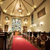 ステンドグラスからの敬虔な光に包まれる教会内は、高いアーチ型のボールト天井、アンティークのシャンデリア、漆喰仕上げの内壁など、神聖さと温かみを醸し出す、クラシカルな雰囲気です。