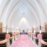 チャペルの装花をピンクに! ベーシックカラーの白い花のコーディネートとは、また違った印象に変わります。
