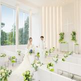 3面ガラス張りの窓から、緑と陽光が溢れる純白のチャペル。 まるで自然の中で誓いを立てているような、そんな気持ちに…。