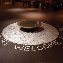 会場入口の水面の花と石文字はアレンジ自在