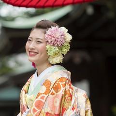 人気の和装+洋髪の花嫁スタイリング例。ヘッドドレスは小花を集めてボリュームを出し、右サイドにはピンクのタッセルを使ってモダンな雰囲気に。色打掛の下に着る「掛け下着」は淡いグリーンでおしゃれ上級者の装いに