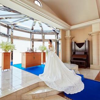 広々とした祭壇の向こう側には自然の光と広大な大自然、さらには富山の水の恵みが二人の未来を祝福。バージンロードのモザイクタイルが柔らかな自然光をさらに感動的な演出へと導きます。 ロイヤルブルーのカーペットがさらに高貴な雰囲気へと変えてくれます。