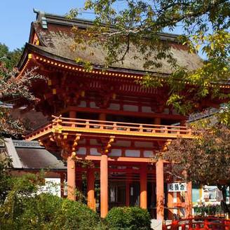 境内奥に見える本殿入り口の朱楼門。錆朱の色彩が 緑の木々や白砂と相まって神聖な雰囲気があります。