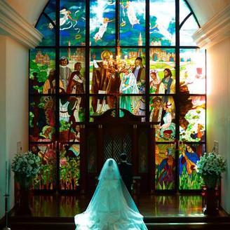 ステンドグラスの迫力、差し込む幻想的な光、ドレスを美しく魅せるための聖壇の高さとバージンロードの広さ、すべての魅力を詰め込んだ一枚。