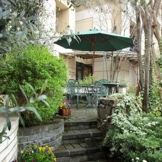 緑や草花が彩るホテルのエントランス。都会の喧騒を忘れさせる癒しの雰囲気が漂う隠れ家ホテル。
