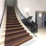 入り口からオシャレな大階段とピアノ。