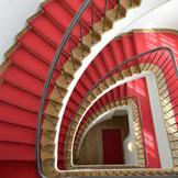 陽光が差し込む螺旋階段は 5階まで続く赤絨毯はクラシカルな雰囲気