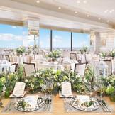 """【GINGA/100名様迄】 ホテル最上階に位置し会場両側に大きな窓が広がる。""""The symphony garden""""をコンセプトにしたこの会場は、主役のおふたりもゲストも肩肘張らずにリラックスして過ごせる空間をつくりあげる。"""