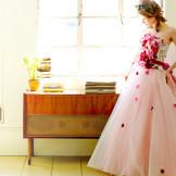 多色のお花を立体的に造作した、キュートなドレススカートはチュールとオーガンジーを重ねてボリューム感を生み、さらに、お花を散りばめることで可憐さを演出しています。お顔周りも華やぎ、主役にふさわしい一着です。