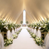 太陽の光が祭壇から射し込み、プリズム型の天井に祝福の調べが響く。まっすぐに伸びた大理石のバージンロード。水のヴェールをまとった十字架に誓う清らかな愛。セレモニーの感動と花嫁の美しさを際立たせるナチュラル&モダンなチャペルです。