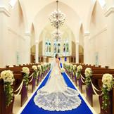 120年の歴史を誇るステンドグラスは圧巻。ロイヤルブルーのバージンロードが花嫁の純白のドレスを美しく魅せます