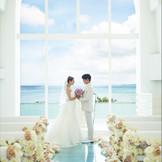 陽光の降り注ぐ大きな窓の向こうの美ら海へと続くかの様なエメラルドブルーの琉球ガラスで作られたスペシャルなバージンロード