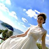 純白のウェディングドレスに身を包み、蒲郡のシンボル「竹島」をバックにワンショット。