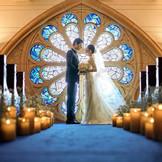 先輩花嫁がアフロディテの中で一番好きな場所No.1のステンドグラス。めずらしいブルーグラデーションのステンドグラスはドレス姿がシルエットのように浮かび上がりまるで映画の1シーンのよう。