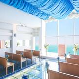 空と海のブルーに包まれた光が降る注ぐオーシャンビューチャペル 【ベルローズ】収容人数/~70名様。絶景のロケーションははもちろん、海リゾート感を味わえる。海へと続くガラスのバージンロードにも注目