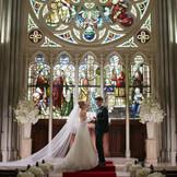 バラ窓のステンドグラスの前で永遠の愛を誓う。