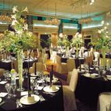 天井高を生かした背の高い装花が美しく映える。シックでスタイリッシュなコーディネートがおすすめ。