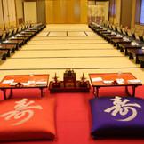 【大広間】 大広間【慶春殿】は舞台付。 高砂席は緋もうせんに金屏風、ぼんぼり、装花で和装ならではの絢爛豪華な披露宴の演出が可能です。