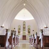 天井高8m、館内とは思えないほど贅沢に設計されたブランチャペル。優しく輝くステンドグラスと温もりある調度品が、厳かな挙式に上質さをプラスしてくれる。