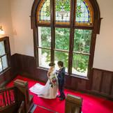 ステンドグラスと赤じゅうたんが演出するクラシックな空間にウエディングドレスが美しく映える