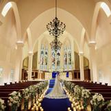 足を踏み入れた瞬間から別空間が広がるチャペル。ブルーのバージンロード×シャンデリア×ステンドグラスは都内でも珍しい大聖堂でご案内
