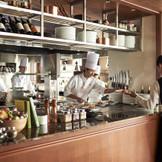 パーティ会場すぐ隣にあるフルオープンキッチンからは、リズミカルな調理音や香りが漂い、お料理への期待がより一層高まる。