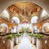 中央奥の大階段から登場する挙式スタイルは、花嫁の美しさや歓びの表情を引き立ててくれると人気。