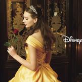 ベルの象徴的なカラー、黄色のドレス。オフショルダーと緞帳のようなドレープスカートでベルっぽさを演出。上品なエアリーツイル素材で、全体的に大人っぽく、エレガントな雰囲気を醸し出して。(c)Disney