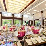 壁一面のガラス扉からガーデンの緑が見渡せる明るくモダンなパーティー会場。開放感あふれるパーティーを。