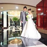 1階ロビー  タキシードとドレスが映えるホテルらしいシックな雰囲気