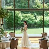 緑と光があふれるパーティー会場。花嫁姿がより一層緑に映える。歩いている姿も美しく映ります。