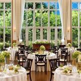 ヴィラ・フォーレ:森の別荘をテーマに皆様にナチュラルな雰囲気の中で披露宴をお楽しみ頂けます。お2人の後方に広がる緑と天井の高さが開放的な印象を与えます。最大収容人数150名