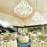 窓から差し込む陽光と緑、煌びやかなシャンデリアが上質な祝宴を予感させる