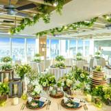 """[24Fスカイテラス]オープンキッチン付きの貸切会場。コンセプトは""""THE SKY RESORT-素晴らしい景色 特別な時間を特別な場所で-""""。両面のガラス窓から美しい景色が一望できる大空の特等席"""