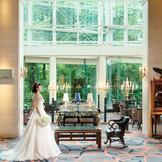 【ホテルロビー】吹き抜けのロビーラウンジからは窓一面に緑が広がり、季節の移ろいとともに色合いも変化する。